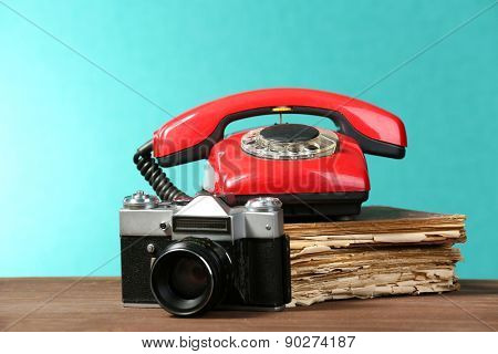 Retro camera with old book and telephone on table on green background