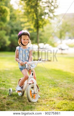 Girl In Pink Helmet Sitting On Her Bike In A Sunny City Park
