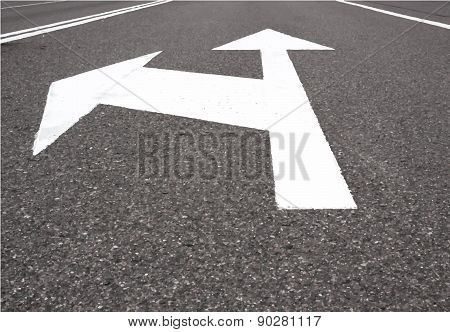 White arrow show left and straight on black asphalt road.