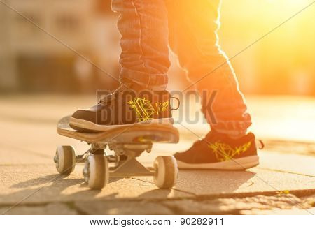 Child with skateboard on the street at sunset light.