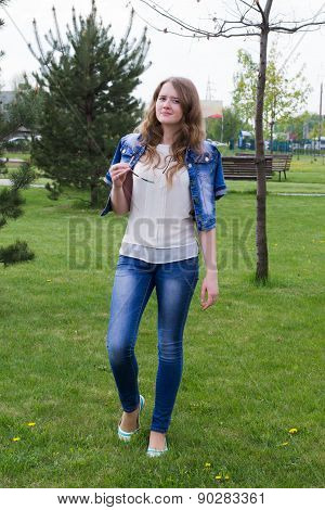 Young Girl In Jeans Standing On The Grass