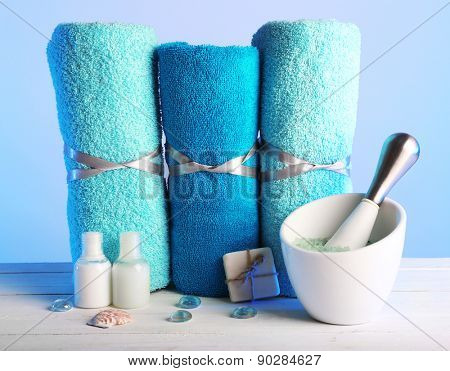 Rolled towels with sea salt, small plastic bottles of shampoo, bar of soap and crystals on wooden table and light colorful background