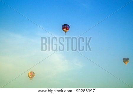 Three Hot Air Balloons Flying Above Morning Fog