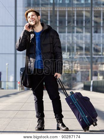 Smiling Man At Station With Bag Talking On Mobile Phone