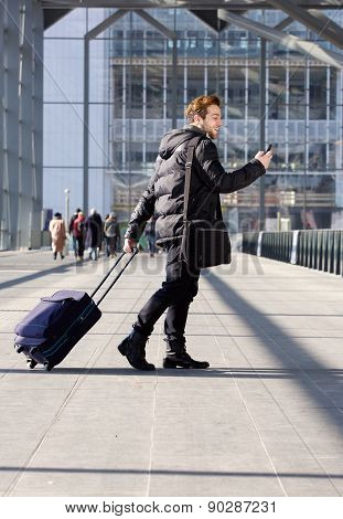 Man Walking With Bag And Mobile Phone At Station