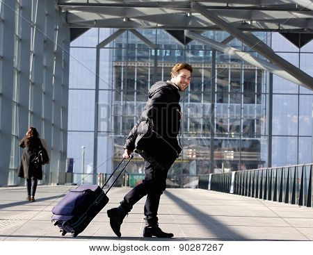 Smiling Young Man Walking With Luggage At Station