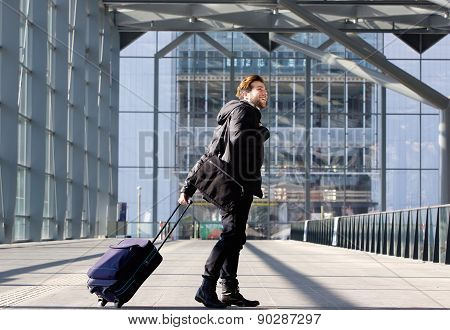 Happy Young Man Walking With Suitcase At Station