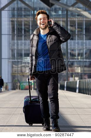 Man Laughing On Mobile Phone While Walking With Luggage