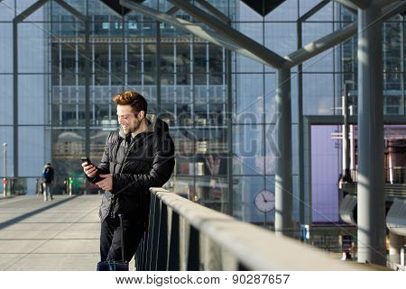 Happy Man Waiting At Station And Looking At Mobile Phone