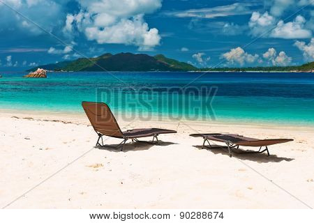 Tropical beach at Seychelles with chaise lounge