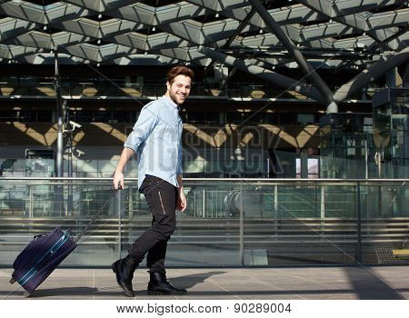 Smiling Male Traveler Walking With Suitcase