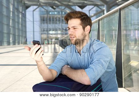Man Looking At Mobile Phone With Confused Expression