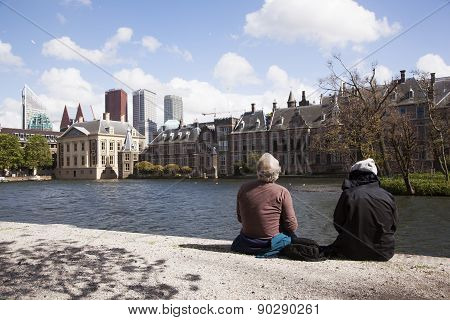 Men Sit And Look At Mauritshuis And Binnenhof In The Hague