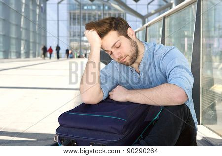 Tired Man With Bag Sleeping At Airport