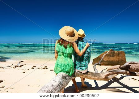 Couple relaxing on a tropical beach Anse Source d'Argent at Seychelles, La Digue.