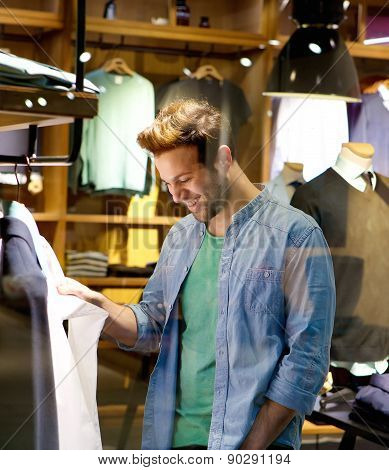 Happy Man Shopping For Clothes At Shop