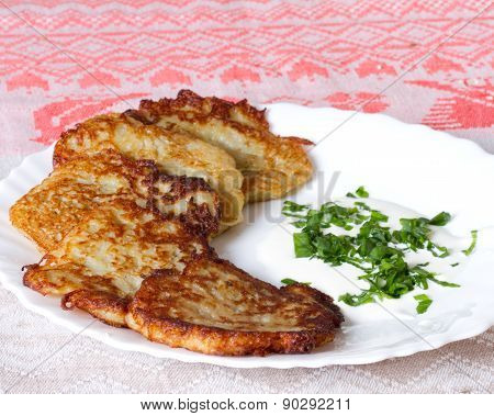 Potato Pancakes On A White Plate With Sour Cream And Garlic Sauce