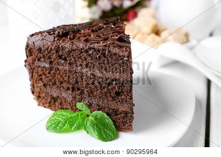 Piece of delicious chocolate cake in plate on color wooden table background