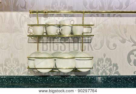 Closeup of white plates in a cupboard.