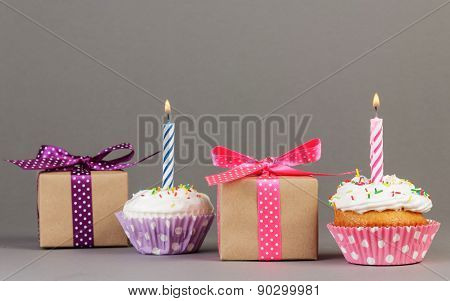 Cupcakes with candles and gift boxes