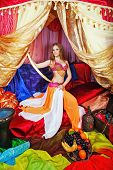 stock photo of harem  - Sexy oriental beauty in a tent and sword in hand abuts her hip - JPG