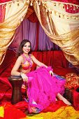 stock photo of harem  - Sexy oriental beauty rests his hand on the tabla - JPG