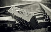 picture of old suitcase  - Not the color image of two old forgotten suitcases on rails.