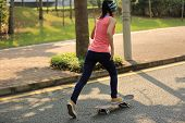 pic of skateboard  - one young asian woman skateboarder skateboarding outdoor - JPG