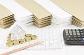stock photo of piles  - House on pile of gold coins as triangle with pencil and calculator on finance account have pile of paperwork with envelope as background - JPG