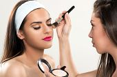 picture of face-powder  - Makeup artist applying powder on a beautiful young woman - JPG
