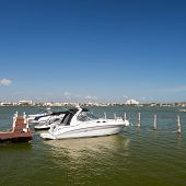 stock photo of jetties  - Speedboats moored to a jetty at tropical lagoon - JPG