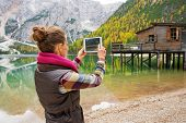 stock photo of pier a lake  - Seen from behind a brunette woman takes a photo of the scenery on Lake Bries - JPG