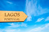 picture of lagos  - Wooden arrow sign pointing destination LAGOS PORTUGAL against clear blue sky with copy space available - JPG