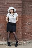 stock photo of blouse  - Pretty young fashion brunette woman in a white hat blouse and black skirt posing outdoor in old vintage brown brick wall background - JPG