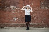 stock photo of blouse  - Photo of a woman in a white hat blouse and black skirt standing against the backdrop of an old vintage brown brick wall - JPG