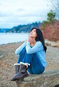 pic of biracial  - Young biracial teen girl in blue shirt and jeans sitting on boulder or rock along lake shore praying face upward to sky - JPG