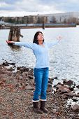 picture of praises  - Young biracial teen girl in blue shirt and jeans arms lifted and outstretched praising God on rocky shore by lake on cloudy day - JPG