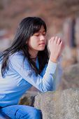image of biracial  - Young biracial teen girl in blue shirt and jeans quietly sitting outdoors leaning on rocks praying - JPG
