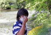 foto of allergy  - young boy with pollen allergy with handkerchief in hand - JPG