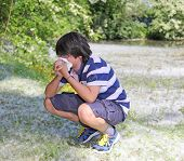 image of allergy  - young boy with pollen allergy with handkerchief in hand - JPG