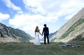 picture of married  - Married couple admiring the landscape above the mountains holding by hands together - JPG