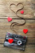 picture of magnetic tape  - Audio cassette with magnetic tape in shape of heart on wooden background - JPG
