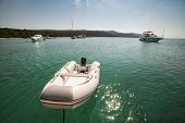 stock photo of outboard  - inflatable motorboat in the sea connected for yacht Croatia - JPG