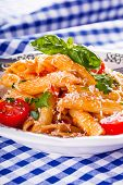 image of pene  - Plate with pasta pene Bolognese sauce cherry tomatoes parsley top and basil leaves on checkered blue tablecloth. Italian and Mediterranean cuisine