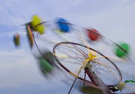 pic of carnival ride  - A carnival ride in motion with the carriages a blur as they spin - JPG