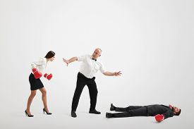 image of referee  - referee holding angry businesswoman in boxer gloves and counting down to knocked out businessman over light grey background - JPG