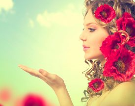 image of hair blowing  - Beauty girl with red poppy flowers hairstyle and open hands - JPG