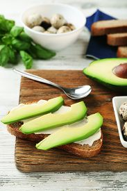 picture of boil  - Slice of rye bread with sliced avocado and boiled quail eggson color wooden background - JPG