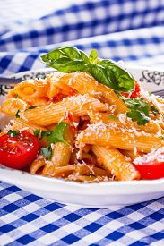 picture of pene  - Plate with pasta pene Bolognese sauce cherry tomatoes parsley top and basil leaves on checkered blue tablecloth. Italian and Mediterranean cuisine ** Note: Shallow depth of field - JPG