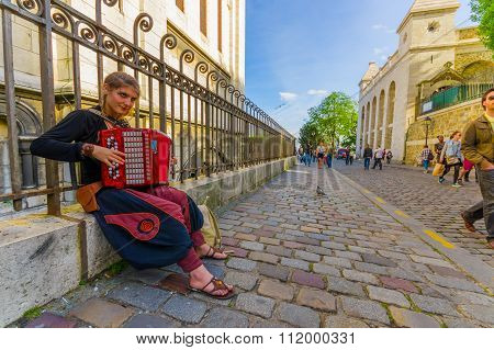 Beautiful young woman playing accordion in the streets of Montmartre, Paris, France